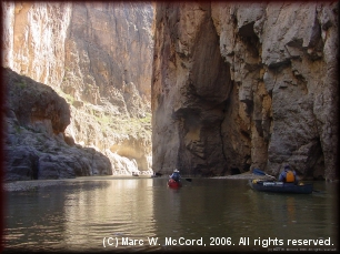Canyon walls tower above canoeists